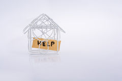 Little wired metal model house and the word HELP Royalty Free Stock Images