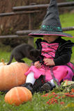 Little witch. With a black kitten Royalty Free Stock Image