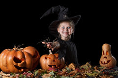 Little witch enthusiastically holding a spider Royalty Free Stock Images