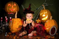 Little witch girl child laughing among pumpkins and candles. Stock Photos