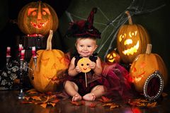 Little witch girl child laughing among pumpkins and candles. Royalty Free Stock Photography