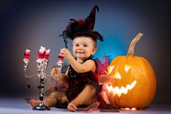 Little witch girl child laughing among pumpkins and candles. Stock Image