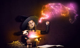 Little witch. Little Halloween witch reading conjure from magic book above pot Stock Photography