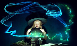 Little witch. Little Halloween witch reading conjure from magic book above pot Royalty Free Stock Photo
