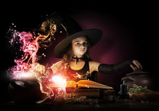 Little witch. Little Halloween witch reading conjure from magic book above pot Stock Photos