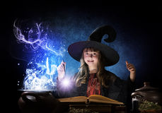 Little witch. Little Halloween witch reading conjure from magic book above pot Royalty Free Stock Image