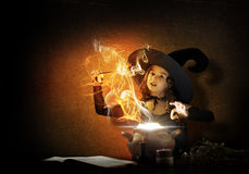 Little witch. Little Halloween witch reading conjure from magic book above pot Stock Images