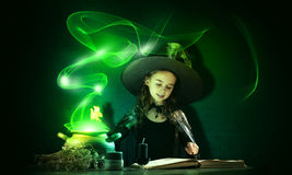 Little witch. Little Halloween witch reading conjure from magic book above pot Stock Photo