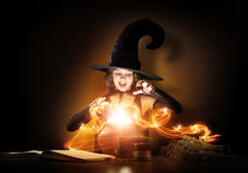 Little witch. Little Halloween witch reading conjure from magic book above pot Stock Image