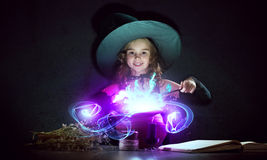 Little witch. Little Halloween witch reading conjure from magic book above pot Royalty Free Stock Photography