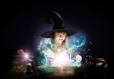 Little witch. Little Halloween witch reading conjure from magic book above pot Royalty Free Stock Images