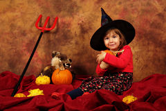 Little witch is having fun for Halloween with pumpkins and hat Royalty Free Stock Images