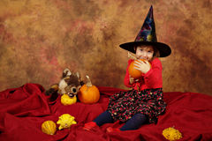 Little witch is having fun for Halloween with pumpkins and hat Stock Photos
