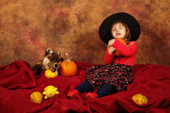 Little witch is having fun for Halloween with pumpkins and hat Stock Image