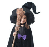 Little witch hiding behind broom Stock Photo