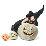 Little witch hiding behind pumpkins Stock Photo