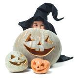 Little witch hiding behind pumpkins Royalty Free Stock Images