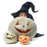 Little witch hiding behind pumpkins. Fun little witch hiding behind pumpkins Royalty Free Stock Images