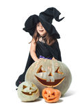 Little witch hiding behind pumpkins Royalty Free Stock Photography