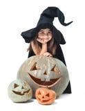 Little witch hiding behind pumpkins. Fun little witch hiding behind pumpkins Stock Photo