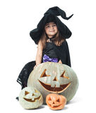 Little witch hiding behind pumpkins Stock Image