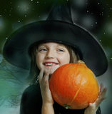 Little witch holding a pumpkin Stock Photography
