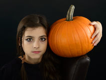 Little witch holding a pumpkin Royalty Free Stock Photography