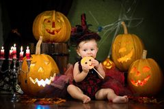 Little witch laughs with candy in the hands among the pumpkins and candles. Stock Image