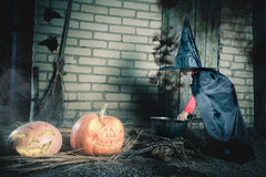 Little witch making a magic potion at Halloween night. Horror. Stock Photography