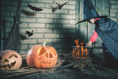 Little witch making a magic potion at Halloween night. Horror. Stock Image