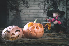 Little witch making a magic potion at Halloween night. Horror. Stock Photo
