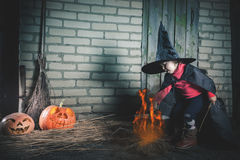 Little witch making a magic potion at Halloween night. Horror. Royalty Free Stock Images