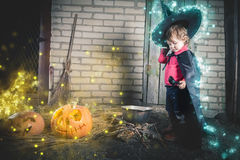 Little witch making a magic potion at Halloween night. Horror. Stock Images