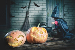Little witch making a magic potion at Halloween night. Pumpkin. Royalty Free Stock Image