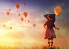 Little witch outdoors. Happy Halloween! Cute little witch with a air ball. Beautiful young child girl in witch costume outdoors Stock Image
