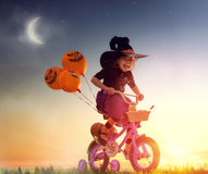 Little witch outdoors. Happy Halloween! Cute little witch with a air ball. Beautiful young child girl in witch costume outdoors Royalty Free Stock Image