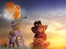 Little witch outdoors. Happy Halloween! Cute little witch with a air ball. Beautiful young child girl in witch costume outdoors Royalty Free Stock Images
