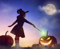 Little witch outdoors. Happy Halloween! Cute little witch with a big pumpkin. Beautiful young child girl in witch costume outdoors Royalty Free Stock Images