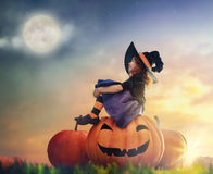 Little witch outdoors. Happy Halloween! Cute little witch with a big pumpkin. Beautiful young child girl in witch costume outdoors Royalty Free Stock Photo