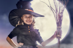 Little witch outdoors. Happy Halloween! Cute little witch with a broomstick. Beautiful young child girl in witch costume outdoors Stock Photography