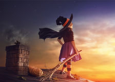 Little witch outdoors. Happy Halloween! Cute little witch with a broomstick. Beautiful young child girl in witch costume on the roof Royalty Free Stock Photo