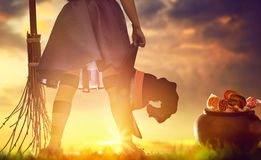 Little witch outdoors. Happy Halloween! Cute little witch with a broomstick. Child girl in witch costume outdoors Stock Photos