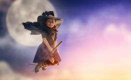 Little witch outdoors. Happy Halloween! Cute little witch flying on a broomstick. Beautiful young child girl in witch costume outdoors Royalty Free Stock Images