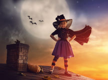 Little witch outdoors. Happy Halloween! Cute little witch on the roof. Beautiful young child girl in witch costume outdoors Stock Photos