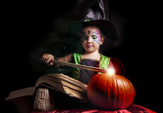 Little witch reads the Book of Spells Stock Photography