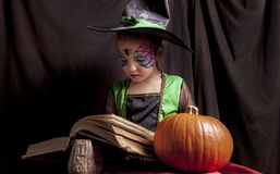 Little witch reads the Book of Spells Royalty Free Stock Images