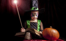 Little witch reads the Book of Spells Royalty Free Stock Photography