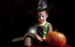 Little witch reads the Book of Spells Royalty Free Stock Image