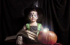 Little witch reads the Book of Spells Stock Image