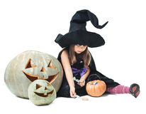 Little witch sits near tykov and considers candies Stock Image